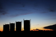 Bitumen Oil Storage Tanks. Silhouetted by the sunset Stock Images