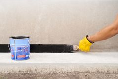 Bitumen waterproofing of the foundation. Worker applies bitumen mastic on the foundation Stock Images