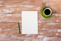 Biura stołowy biurko z dostawami, biały pusty nutowy ochraniacz, filiżanka, pióro, komputer osobisty, miął papier, kwiat na drewn Obrazy Stock