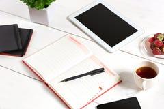 Biura stołowy biurko z setem dostawy, biały pusty notepad, filiżanka, pióro, pastylka, kwiat na białym tle Odgórny widok Zdjęcie Stock