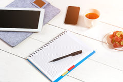 Biura stołowy biurko z setem dostawy, biały pusty notepad, filiżanka, pióro, pastylka na białym tle Odgórny widok Obrazy Stock