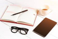Biura stołowy biurko z setem dostawy, biały pusty notepad, filiżanka, pióro, pastylka, szkła na białym tle Odgórny widok Zdjęcie Stock