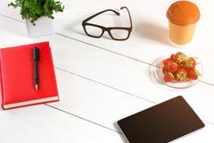 Biura stołowy biurko z setem dostawy, czerwony notepad, filiżanka, pióro, pastylka, szkła, kwiat na białym tle Odgórny widok Zdjęcia Stock