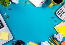 Biura stołowy biurko z setem kolorowe dostawy, biały pusty nutowy ochraniacz, filiżanka, pióro, komputer osobisty, miął papier, k Obrazy Stock