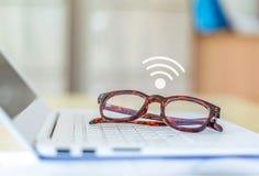 biurka miejsce pracy, eyeglasses z laptopem i wifi ikona na drewnie de, Obraz Royalty Free