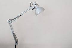 Biurko lampa z białą betonową ścianą jako tło Obraz Royalty Free