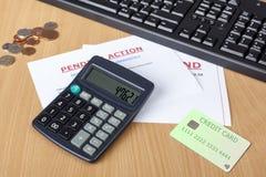 Biurko pokazuje definitywnych żądania z kredytową kartą i kalkulatorem Fotografia Stock
