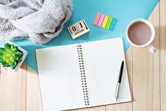 Biurko stół z szalikiem, otwarty notatnika papier, sześcian filiżanka, kalendarz, Odgórny widok i mieszkanie, kłaść z kopii przes Fotografia Stock