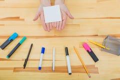 Biuro stół z akcesoriami: biały prześcieradło papier, menchia markier, szkło kawa, pióro, ołówek i kobiety, zdjęcia stock