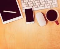 Biuro stół z cyfrową pastylką, smartphone i filiżanką kawy, na widok Fotografia Royalty Free