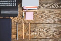 Biuro stół z notepad, dostawami, laptopem i stertą książki, Widok od above z kopii przestrzenią obrazy stock