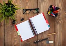 Biuro stół z notepad, kolorowymi ołówkami, dostawami i kwiatem, Obraz Stock