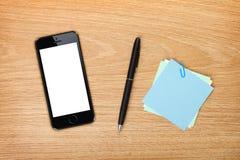 Biuro stół z telefonem komórkowym i dostawami Fotografia Royalty Free