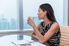 Biurowa kobieta pije kawowy myślący relaksować Fotografia Royalty Free