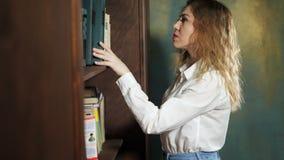 Biurowa kobieta wybiera książkę dla czytelniczej pozycji blisko półki na książki zbiory wideo