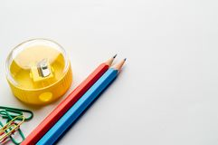 Biurowe dostawy - ołówki, ołówkowa ostrzarka, papierowe klamerki na białym tle obraz royalty free