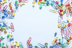 Biurowe dostawy w postaci barwionych guzików i papierowych klamerek na krawędziach fotografia Obraz Stock