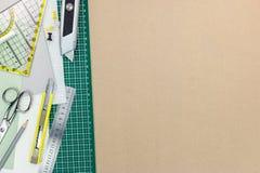 Biurowe dostawy, zielona rozcięcie mata na brązie przetwarzali papierowego backg Obraz Stock