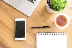 Biurowego biurka drewniany stół z mądrze telefonem, filiżanką herbata, laptopem, piórem, rośliną i notatnikiem, Odgórny widok z k Zdjęcie Royalty Free
