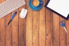 Biurowego biurka egzamin próbny w górę szablonu z pastylką, klawiaturą i kawą na drewnianym tle,
