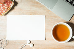 Biurowego biurka stół z laptopem, herbatą i kanapką z kiełbasą, Odgórny widok Zdjęcia Stock