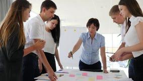 Biurowi ludzie dyskutuje pomysłu rozwój biznesu w sala konferencyjnej obok biurka zbiory