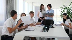 Biurowi ludzie z dokumentami w ręce mówją na spotkaniu w nowożytnej sala posiedzeń w centrum biznesu