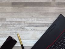 Biurowy biurko z czarnym laptopem, złoty colour telefon komórkowy, złoty luksusowy pióro na białym drewnianym tekstury tle zdjęcie stock