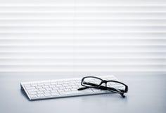 Biurowy biurko z komputerów osobistych szkłami i klawiaturą Fotografia Royalty Free