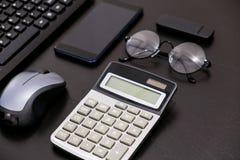 Biurowy czarny biurko stół z komputerem, kalkulator, smartphone, szkła, niecka, dostawy Odgórny widok z kopii przestrzenią Obraz Royalty Free