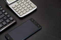 Biurowy czarny biurko stół z komputerem, kalkulator, smartphone, szkła, niecka, dostawy Odgórny widok z kopii przestrzenią Obraz Stock