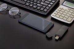 Biurowy czarny biurko stół z komputerem, kalkulator, smartphone, szkła, niecka, dostawy Odgórny widok z kopii przestrzenią Zdjęcia Stock