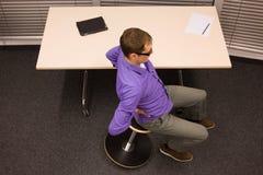 Biurowy joga - biznesowy mężczyzna ćwiczy przy biurkiem Obraz Stock