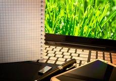 Biurowy miejsce pracy z notatnikiem, mądrze telefonem, piórem, błysk przejażdżką i wordpad z zielonej trawy tłem, Obraz Royalty Free