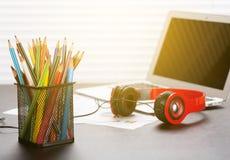 Biurowy miejsce pracy z z laptopem, hełmofonami i ołówkami, Obraz Stock