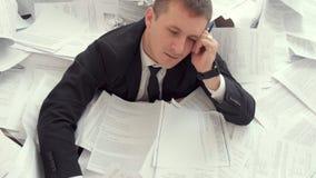 Biurowy pracownik no może podołać z liczbą dokumenty Zmęczony pracownik siedzi na górze dokumenty zbiory