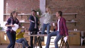 Biurowy przyjęcie, szalona kreatywnie drużyna pracowników mężczyźni i kobiety ma zabawę w kuchni w, biurze i miotaniu podczas gdy zbiory