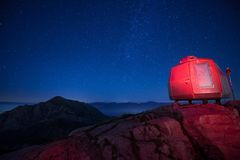 Bivacco rosso nelle montagne alte sotto un bello cielo stellato fotografia stock