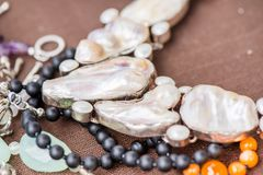 Biwa pearl necklace laying on natural brown linen tablecloth. stock photos
