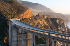 Bixby arch bridge in sunset light. Winding arch bridge on Cabrillo highway next to Big Sur state park in sunset light with mountains and ocean on a back side Royalty Free Stock Photo