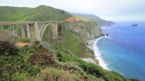Bixby Bridge near Big Sur. View of concrete arch bridge over gorge with mountains on one side and cliffs down to ocean on the other stock photo