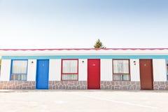 Motel met rode en blauwe deuren stock afbeeldingen