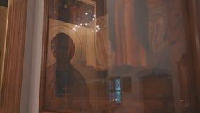 Bizarre bezinningen over het glas die het pictogram in Orthodox Christian Church behandelen Sluit omhoog stock videobeelden