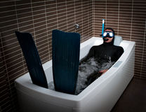 Bizarre diver with flipper in bathroom. Economical crisis holiday royalty free stock photo