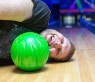 Drunk man on bowling alley. Bizarre drunk man lying on bowling alley Royalty Free Stock Photography