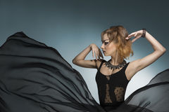 Bizarre fashion woman. Fashion portrait of bizarre dark lady with gothic style, strong make-up and rock accessories wearing and big veil flying skirt. Carnival Stock Images