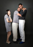 Bizarre gay couple with incredulous girlfriend. Gray background stock image