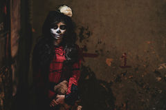 Bizarre girl. Portrait of bizarre girl with scull face standing in dark corner royalty free stock photo