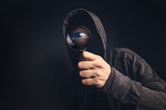 Bizarre hooded spooky person with magnifying glass. Focus on enlarged eye peeking at you Royalty Free Stock Photo