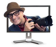 Bizarre man with camera looks out from monitor Stock Image